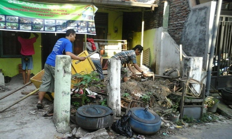 Suasana kerja bakti membersihkan lingkungan sekitar